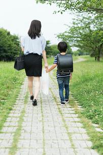 買い物袋を持って歩く親子の後ろ姿の写真素材 [FYI02568403]