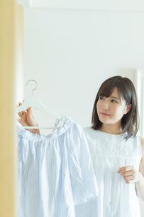 クローゼットから服を取り出す女性の写真素材 [FYI02568407]