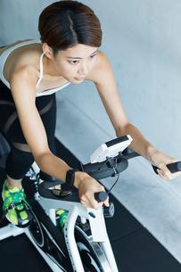 ジムでエアロバイクを漕ぐ若い女性の写真素材 [FYI02568468]