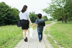 買い物袋を持って歩く親子の後ろ姿の写真素材 [FYI02568509]
