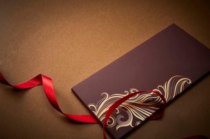 ゴールドの背景に置かれた赤いリボンと茶色い箱の写真素材 [FYI02569139]