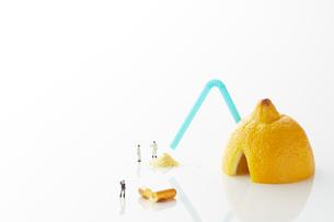 白い天板の上のレモンとビタミン剤とミニチュア人形の写真素材 [FYI02569218]