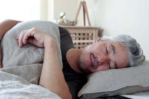 ベッドで眠るミドル男性の写真素材 [FYI02569247]