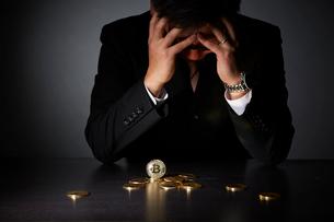 ビットコインでビジネスに失敗し頭を抱えるスーツを着た男性の写真素材 [FYI02569253]