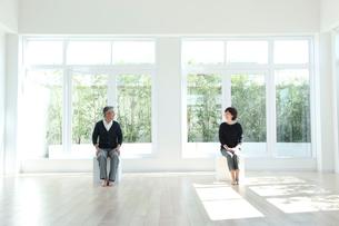 窓のある部屋に座るミドルカップルの写真素材 [FYI02569276]