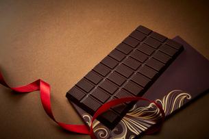 ゴールドの背景に置かれた赤いリボンと板チョコの写真素材 [FYI02569352]