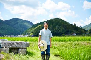 畦道に立つ笑顔の男性の写真素材 [FYI02569423]