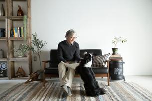 ソファで愛犬と過ごすシニア男性の写真素材 [FYI02569531]