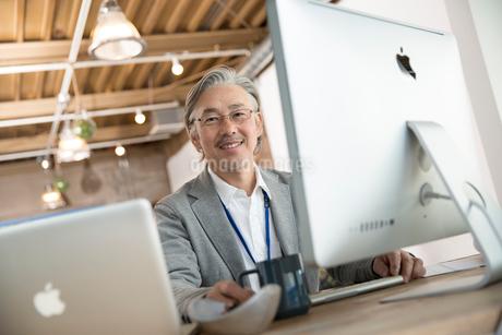 デスクで仕事をするシニアビジネスマンの写真素材 [FYI02569619]
