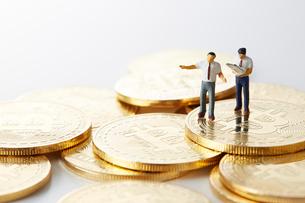 ビットコインの上のミニチュアのサラリーマンの写真素材 [FYI02569699]