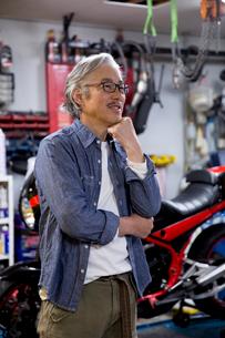 バイクの前で微笑むシニア男性の写真素材 [FYI02569705]