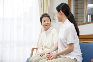座りながら談笑するシニア女性と介護福祉士の写真素材 [FYI02570845]