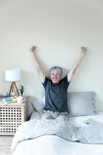 ベッドで伸びをするミドル男性の写真素材 [FYI02570881]