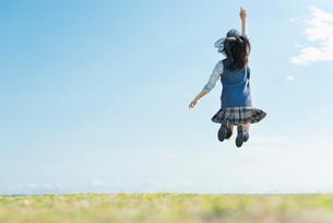 女子高生 海 草原 ジャンプの写真素材 [FYI02570917]