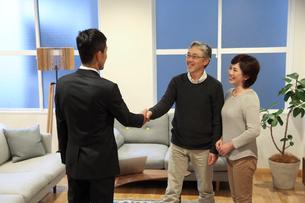 自宅でビジネスマンと握手するミドルカップルの写真素材 [FYI02571035]
