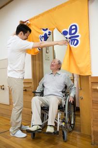介護施設浴場から出る車椅子のシニア男性と介護福祉士の写真素材 [FYI02571051]