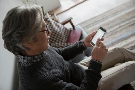ソファでスマートフォンに触れるシニア男性の写真素材 [FYI02571069]