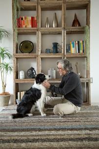 棚の前で愛犬と過ごすシニア男性の写真素材 [FYI02571279]