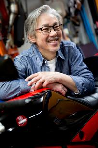 バイクのタンクに重なって微笑むシニア男性の写真素材 [FYI02571362]