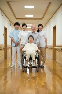 家族と介護施設スタッフに囲まれる車椅子のシニア女性の写真素材 [FYI02571406]