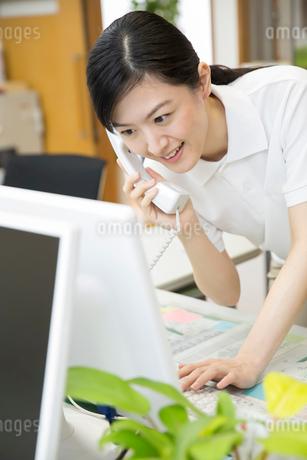 介護施設で電話応対する介護福祉士の写真素材 [FYI02571450]