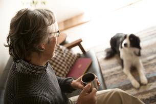ソファで愛犬と過ごすシニア男性の写真素材 [FYI02571530]