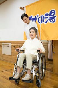 介護施設浴場から出る車椅子のシニア女性と介護福祉士の写真素材 [FYI02571776]