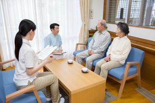 地域包括支援センターで介護福祉士とPTに相談するシニア夫婦の写真素材 [FYI02571884]