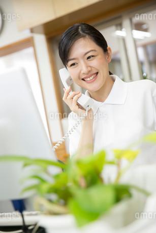 介護施設で電話応対する介護福祉士の写真素材 [FYI02571889]