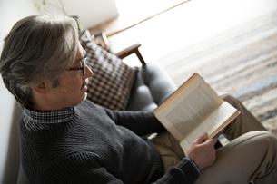ソファで読書するぐシニア男性の写真素材 [FYI02571941]