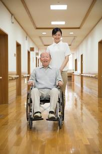 車椅子に座ったシニア男性と介護福祉士の写真素材 [FYI02572012]