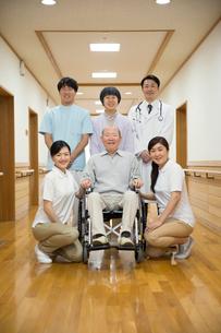 家族と介護施設スタッフに囲まれる車椅子のシニア男性の写真素材 [FYI02572017]