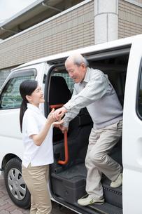 介護福祉士にサポートされ車両から降りるシニア男性の写真素材 [FYI02572059]