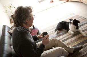 ソファで愛犬と過ごすシニア男性の写真素材 [FYI02572075]