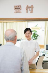 介護施設の受付で応対する介護福祉士の写真素材 [FYI02572114]