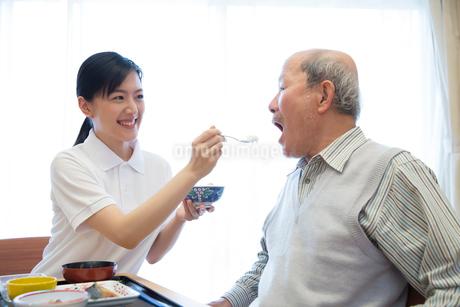 介護施設の朝食を食べるシニア男性とサポートする介護福祉士の写真素材 [FYI02572207]