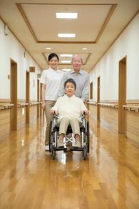 車椅子に座ったシニア夫婦と介護福祉士の写真素材 [FYI02572232]