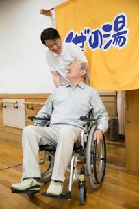 介護施設浴場から出る車椅子のシニア男性と介護福祉士の写真素材 [FYI02572313]