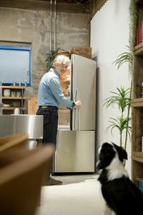 冷蔵庫のドアを開け愛犬と目の合うシニア男性の写真素材 [FYI02572372]