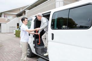 介護福祉士にサポートされ車両から降りるシニア男性の写真素材 [FYI02572418]