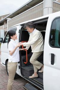 介護福祉士にサポートされ車両から降りるシニア女性の写真素材 [FYI02572432]