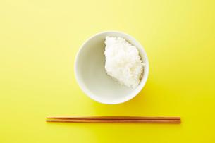 お茶碗に3分の1だけ入れられたご飯と箸の写真素材 [FYI02572460]