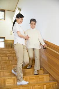 階段で介護福祉士にサポートされるシニア女性の写真素材 [FYI02572489]