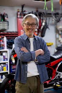 バイクの前で腕を組むシニア男性の写真素材 [FYI02572499]