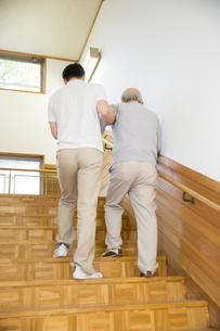 階段で介護福祉士にサポートされる後姿のシニア男性の写真素材 [FYI02572507]