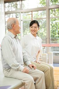 座りながら談笑するシニア男性と介護福祉士の写真素材 [FYI02572534]