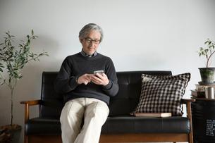 ソファでスマートフォンに触れるシニア男性の写真素材 [FYI02572552]