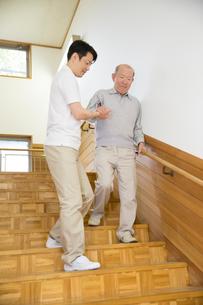 階段で介護福祉士にサポートされるシニア男性の写真素材 [FYI02572607]