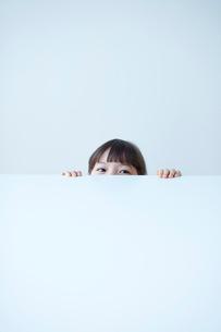 白いテーブルの下から覗く女の子の写真素材 [FYI02572631]