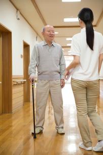 杖で歩くシニア男性と介護福祉士の写真素材 [FYI02572688]